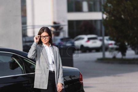 Lächelnde Geschäftsfrau berührt Brille, während sie neben schwarzem Auto steht