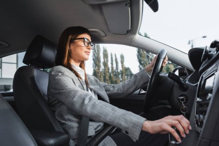 stylish businesswoman in eyeglasses shifting transmission lever while driving car