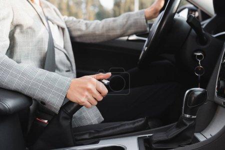 Photo pour Vue partielle du levier de frein à main de la femme d'affaires pendant que la voiture de direction se déplace sur fond flou - image libre de droit