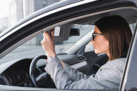 Photo pour Femme d'affaires réglage rétroviseur tout en étant assis dans la voiture - image libre de droit