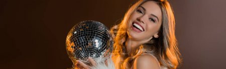 pleased blonde woman holding disco ball on black, banner