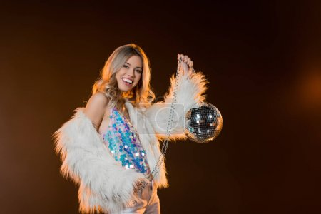 pleased blonde woman in faux fur jacket holding disco ball on black
