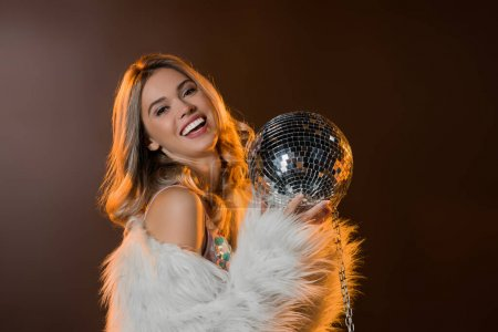 happy blonde woman in faux fur jacket holding disco ball on black