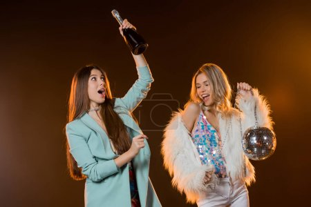surprised woman looking at bottle with champagne near blonde friend with disco ball on black