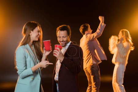 happy woman and african american man holding plastic cups near friends dancing during party on black