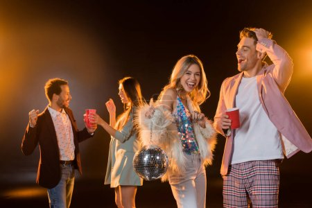happy blonde woman holding disco ball near man with plastic cup and multicultural friends on blurred background on black