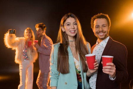 Photo for Cheerful brunette woman and african american man holding plastic cups near friends taking selfie during party on black - Royalty Free Image