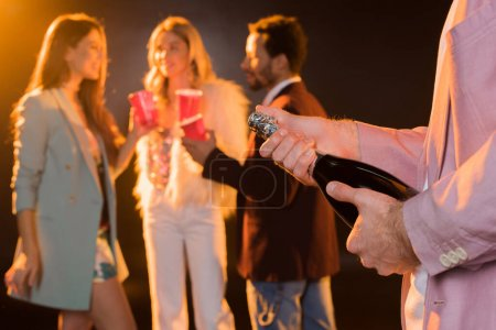 Photo for Man holding bottle with champagne near multicultural friends on blurred black background - Royalty Free Image