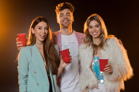 cheerful man and women holding plastic cups during party on black