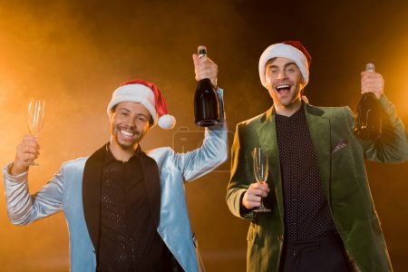 Photo for Excited interracial men in santa hats holding bottles of champagne and glasses on black - Royalty Free Image