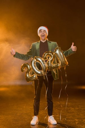 full length of excited man in santa hat showing thumbs up near balloons with 2021 numbers on black
