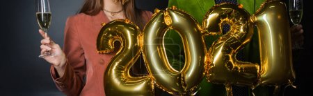 Photo for Partial view of couple holding balloons with 2021 numbers and glasses of champagne on black - Royalty Free Image