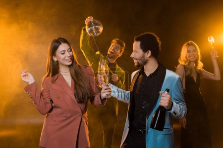 happy multicultural couple holding glasses of champagne and bottle near cheerful friends on blurred and black background