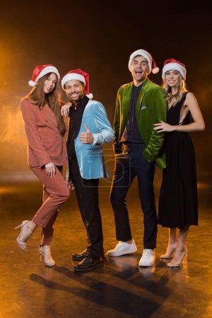Photo pour Pleine longueur d'amis multiculturels heureux chapeaux Santa sur noir - image libre de droit
