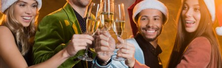 Photo for Happy multicultural friends in santa hats toasting glasses of champagne on black, banner - Royalty Free Image
