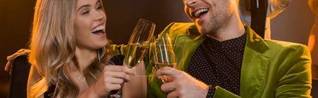 happy couple toasting glasses with champagne and laughing on black, banner