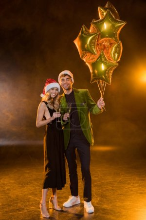Photo for Full length of smiling couple in santa hats holding glasses with champagne and balloons on black - Royalty Free Image