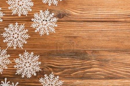 Photo pour Vue de dessus des flocons de neige d'hiver sur fond en bois - image libre de droit