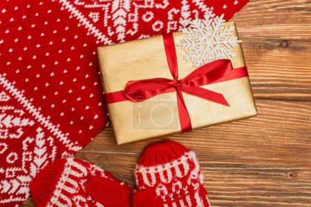 top view of gift box and red knitted scarf and mittens on wooden background