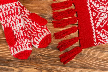 top view of red knitted scarf and mittens on wooden background