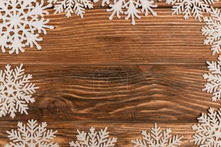 Photo for Top view of winter snowflakes on wooden background - Royalty Free Image