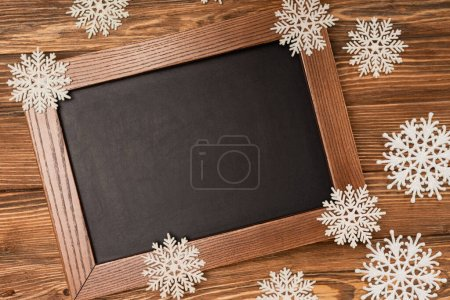 Photo for Top view of winter snowflakes on chalkboard on wooden background - Royalty Free Image