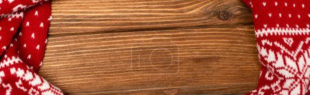 Photo pour Vue du haut de l'écharpe tricotée rouge d'hiver sur fond en bois, bannière - image libre de droit