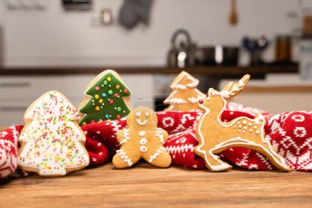 winter gingerbread cookies and scarf on wooden background