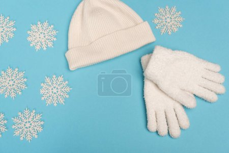 top view of winter white knitwear and snowflakes on blue background