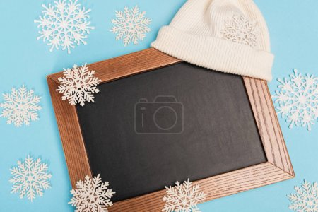 top view of winter white beanie, chalkboard and snowflakes on blue background