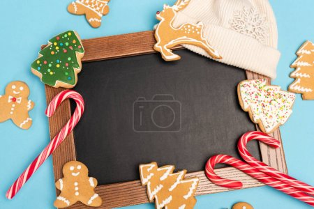 top view of gingerbread cookies and chalkboard on blue background