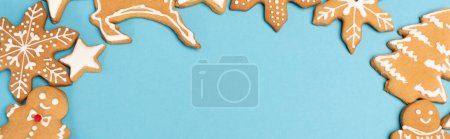 Photo for Top view of winter gingerbread cookies on blue background, banner - Royalty Free Image