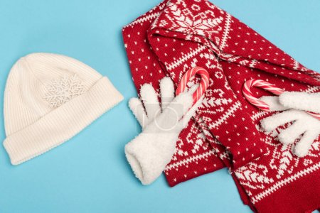 top view of winter accessories and candy canes on blue background