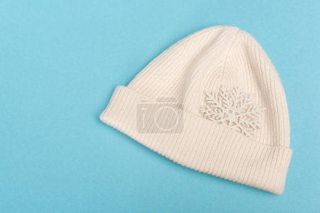 top view of white beanie and snowflake on blue background