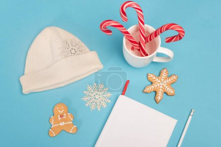 top view of gingerbread cookies, beanie, candy canes and blank notebook on blue background