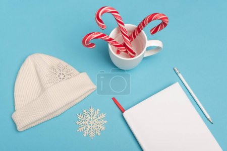 top view of beanie, candy canes and blank notebook on blue background