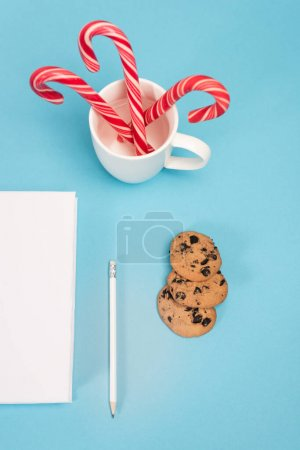 top view of chocolate cookies, candy canes and blank notebook on blue background