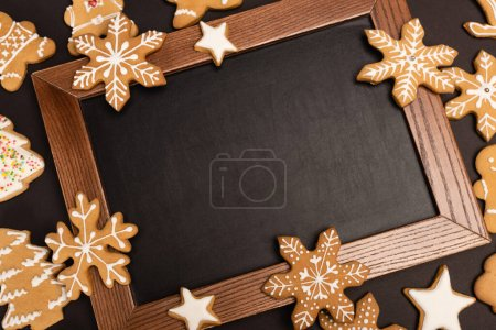 Photo for Top view of gingerbread cookies and chalkboard on black background - Royalty Free Image