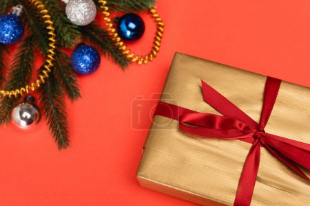 top view of decorated Christmas tree and gift on red background