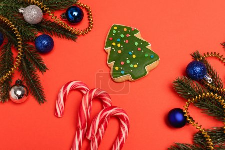 top view of decorated Christmas tree, cookie and candy canes on red background