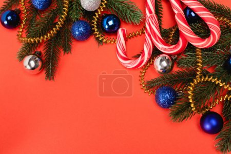 Photo for Top view of decorated Christmas tree and candy canes on red background - Royalty Free Image