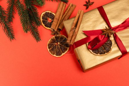 Photo for Top view of Christmas tree, gift with spices on red background - Royalty Free Image