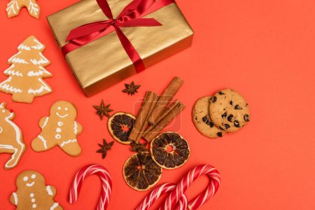 Photo for Top view of gift, candy canes, spices and gingerbread cookies on red background - Royalty Free Image