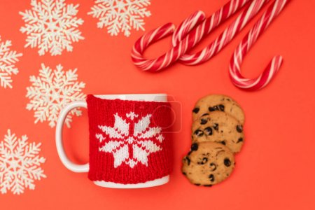 Photo for Top view of chocolate  cookies, candy canes, snowflakes and mug on red background - Royalty Free Image