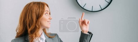 Positive redhead businesswoman pointing with finger and looking at wall clock on grey, banner