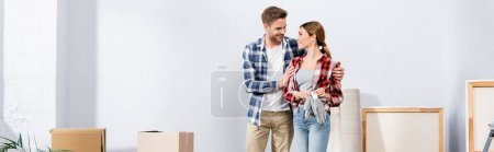 Photo for Happy young man hugging and looking at girlfriend with gloves at home, banner - Royalty Free Image