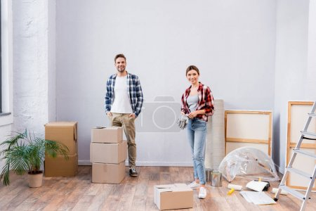 volle Länge des glücklichen jungen Paares, das in die Kamera schaut, während es während der Reparatur im Zimmer steht