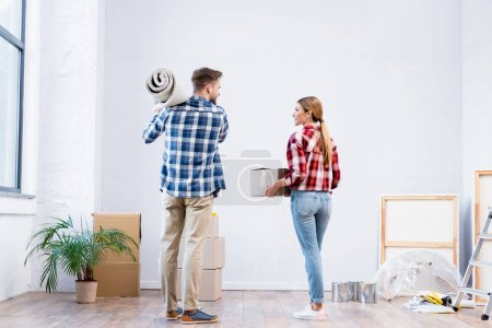 Photo pour Vue arrière du jeune couple tenant la boîte en carton et le rouleau de tapis à la maison - image libre de droit
