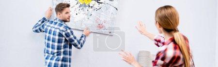 Photo pour Jeune homme regardant la femme gesticuler tout en retirant l'image du mur sur le premier plan flou à la maison, bannière - image libre de droit