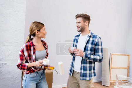 Photo for Happy young couple with coffee cups looking at each other during repair at home - Royalty Free Image